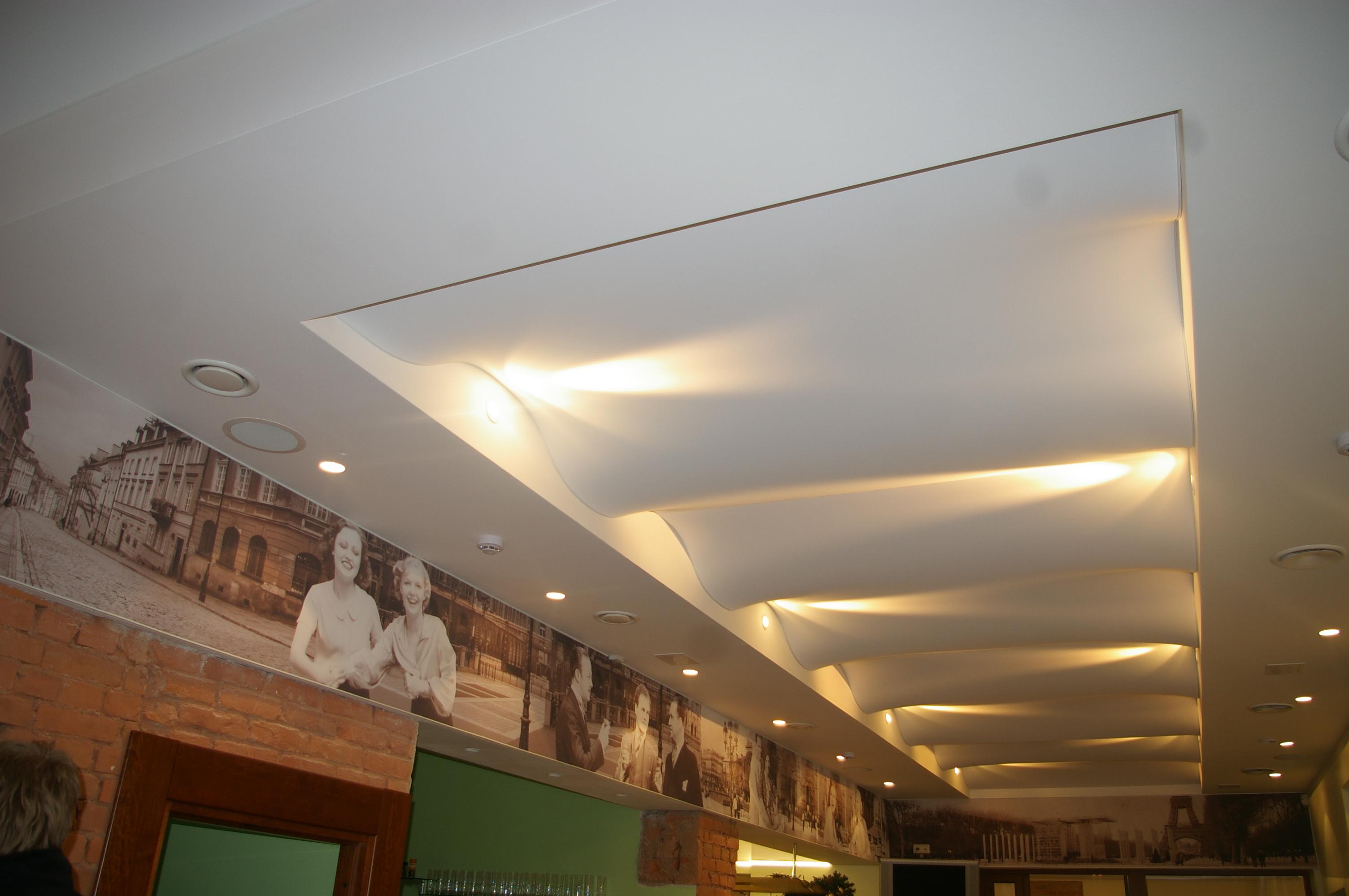 Lygioji lubų dalis per patalpos perimetrą, kurioje sumontuotas 705S CLIPSO audinys, paslėpti rekuperacijos vamzdžiai ir sumontuotas pagrindinis patalpos apšvietimas. Saugant aukštį ir pagyvinant patalpą per vidurį CLIPSO audinys sumontuotos kaip žaismingos bangelės, jomisslystanti šviesa šį įspūdį dar labiau sustiprina. Sienos dekorui panaudotas audinys su spauda pridnegia metalines sijas ir papuošią patalpą.